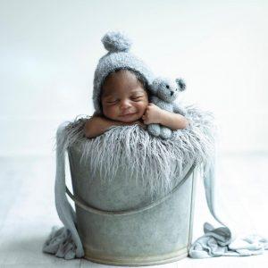 Baby asleep with a teddy bear in a bucket