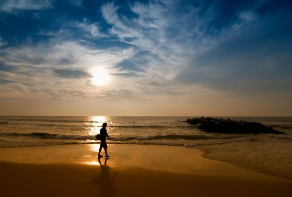 A person is walking on a beach holding a fishing pole with the sun setting behind them over the water.